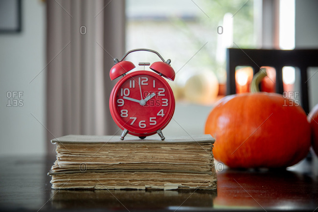 vintage books and red alarm clock with pumpkins on a table