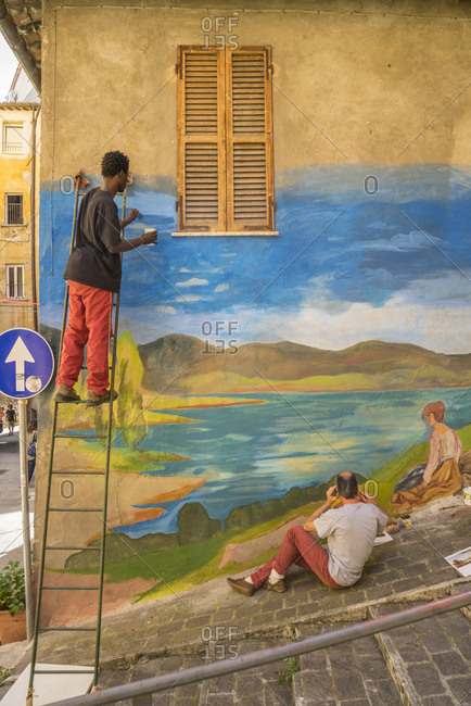"June 18, 2016: Italy, Umbria, Perugia . Via della Viola during ""Alkemika"" street art festival. Artist painting a wall murales inspired by peace and harmony"