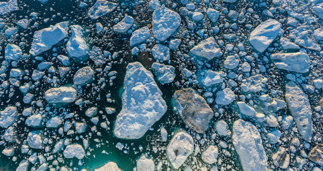 Aerial view above a group of icebergs floating together, Greenland.