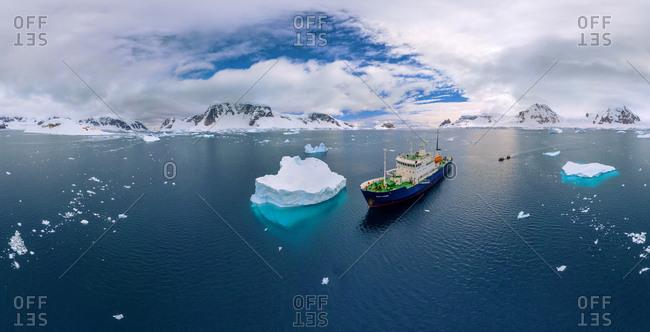 November 27, 2014: Aerial view Polar Pioneer, a scientific ship sailing near to an iceberg in Antarctica.