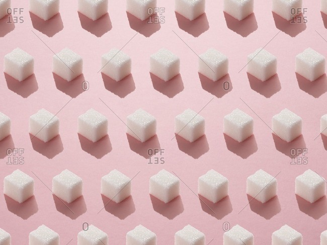 Sugar cubes on pink background.