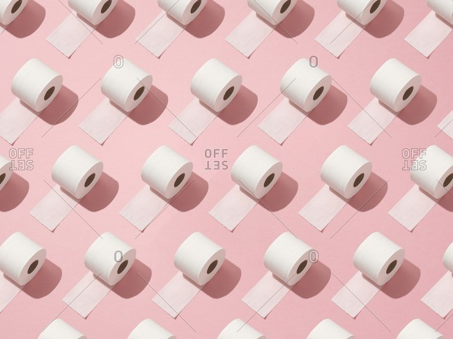 Toilet rolls on pink background.