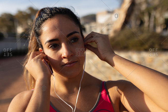 Woman listening to music and exercising in a park