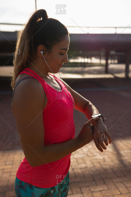 Woman listening to music and checkin her smartwatch