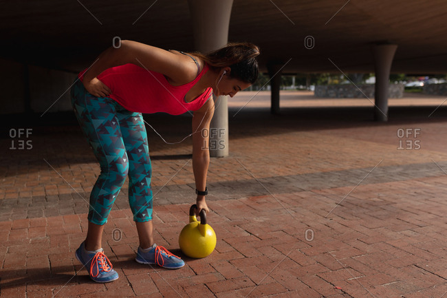 Woman exercising in a park with kettlebell
