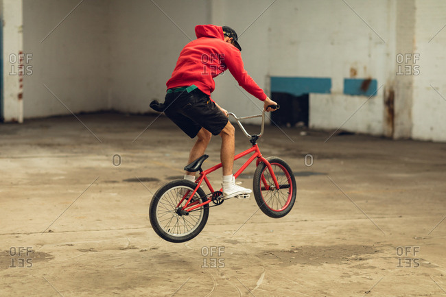 BMX rider in an empty warehouse jumping