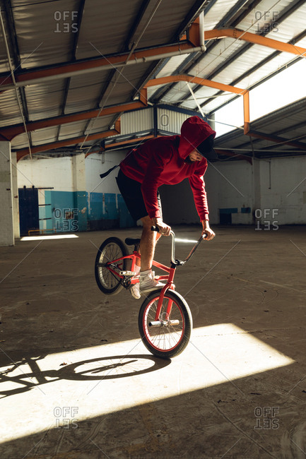 BMX rider in an empty warehouse