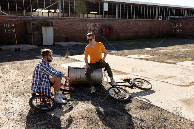BMX riders sitting in a yard talking