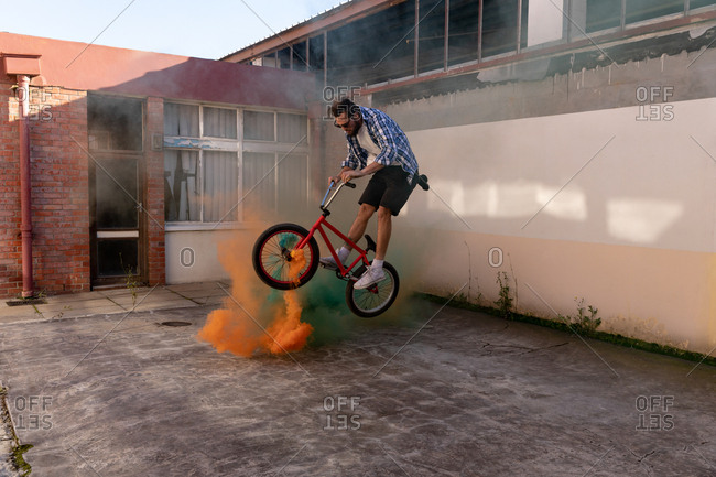 BMX rider jumping over smoke grenades