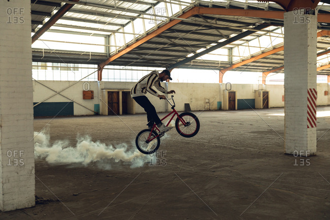 BMX rider in an empty warehouse using smoke grenade