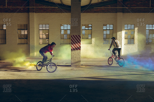 BMX riders in an empty warehouse using smoke grenades