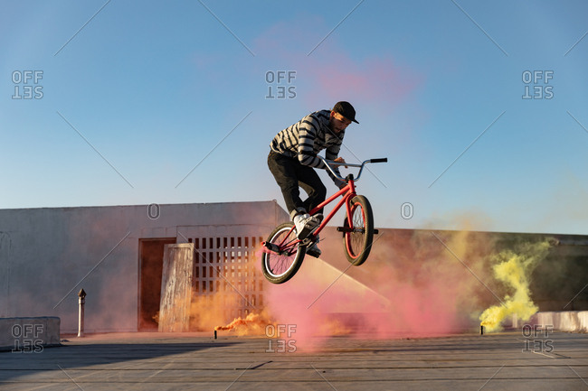 BMX rider on a rooftop jumping and using smoke grenades