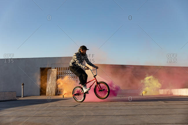BMX rider on a rooftop using smoke grenades