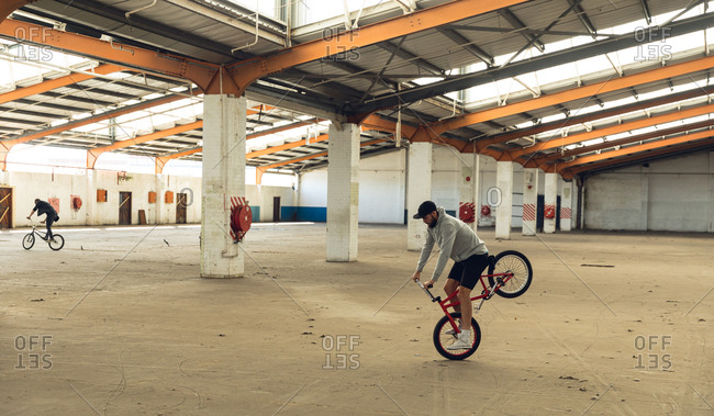 BMX riders in an empty warehouse