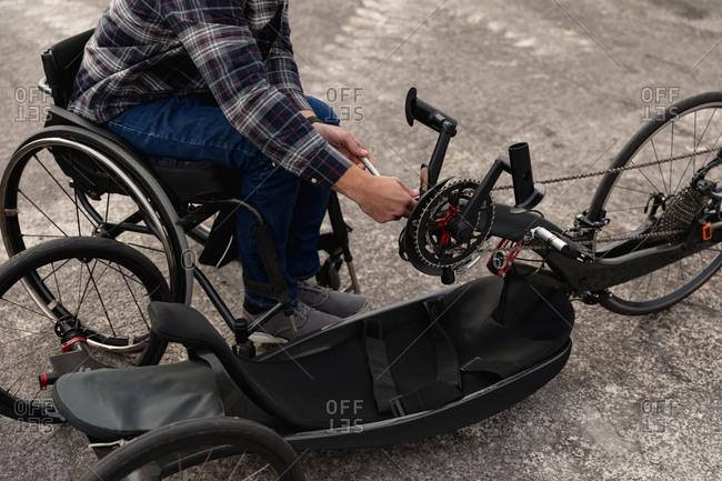 Disabled man in a wheelchair assembling a bike