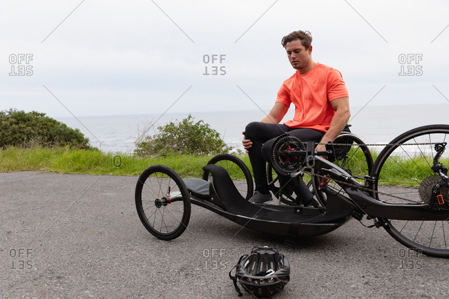Disabled man getting out of a wheelchair into a recumbent bike