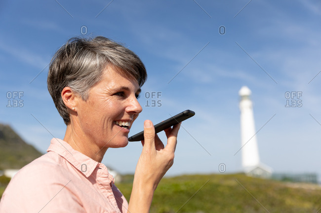 Woman standing near lighthouse using smartphone