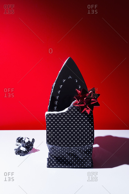 Flat iron wrapped as a gift in polka dot paper with a red bow on red background