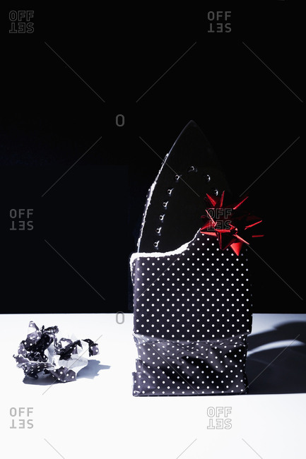 Flat iron wrapped as a gift in polka dot paper with a red bow on black background