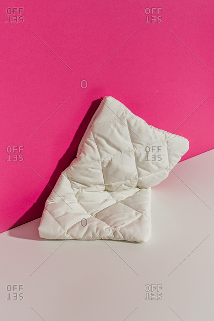 Geometric white handbag against fluorescent pink background