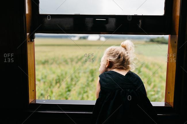 Little girl looking out train window