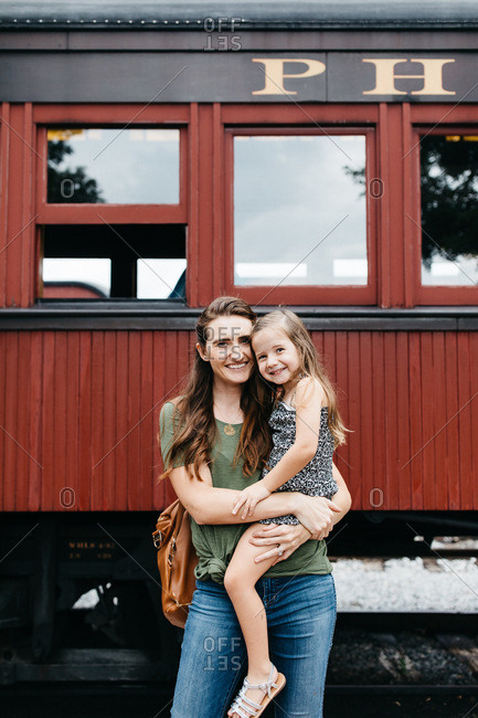 Mom and daughter outside steam train
