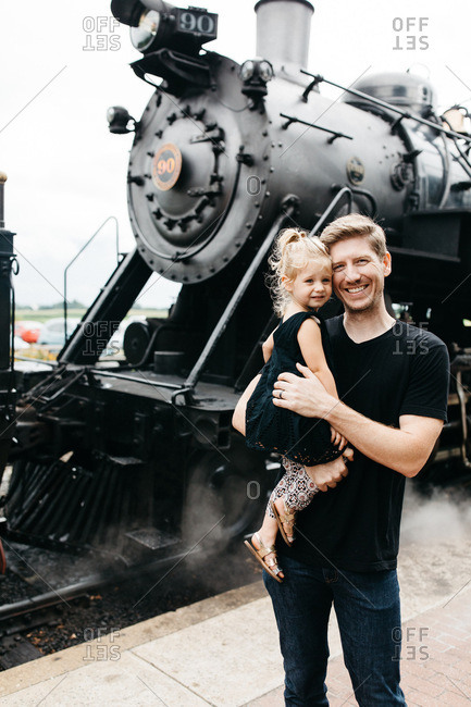 Father posing with daughter by steam train engine