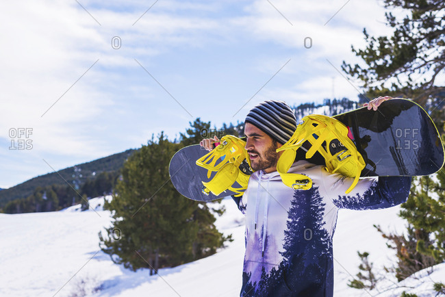 Portrait of man in winter wilderness with snowboard