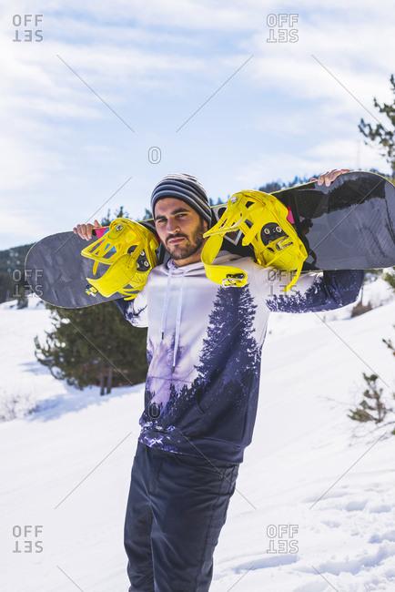 Portrait of man in winter wilderness with snowboard