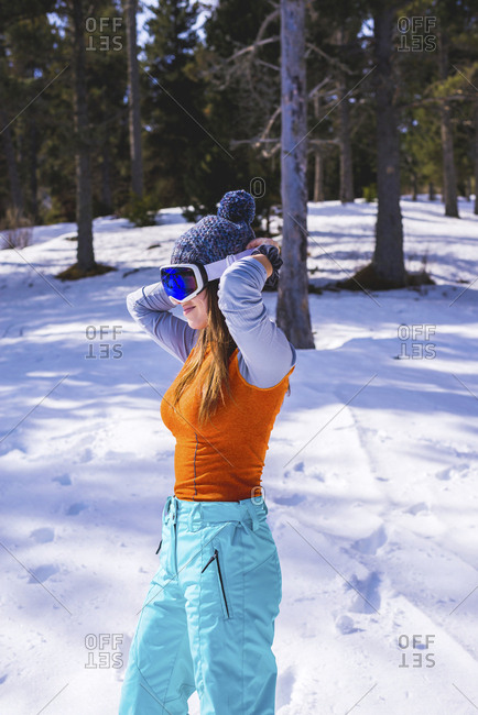 Side view of a woman wearing ski clothing getting ready to ski