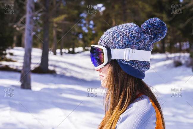 Woman wearing ski clothing standing on snow while looking away to the mountains