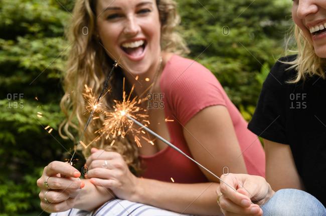 Smiling women holding sparkler - Offset