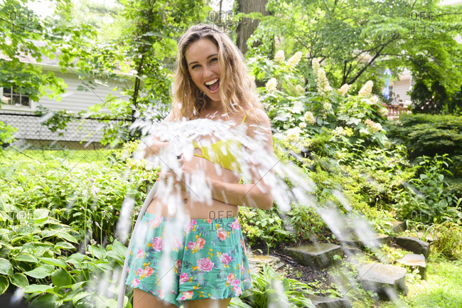Smiling young woman holding garden hose