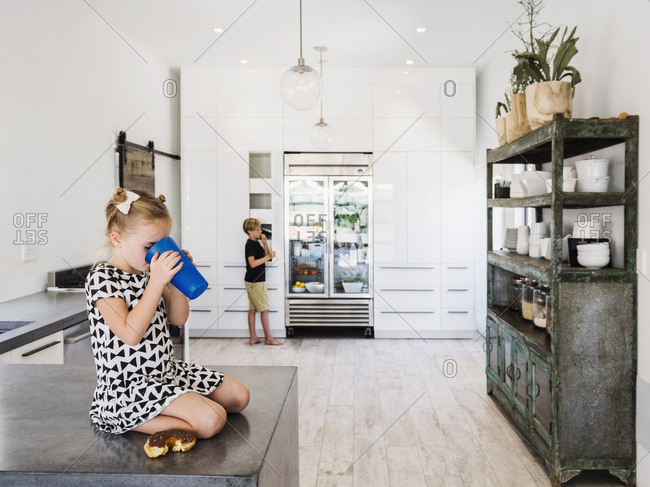 Girl drinking on kitchen counter