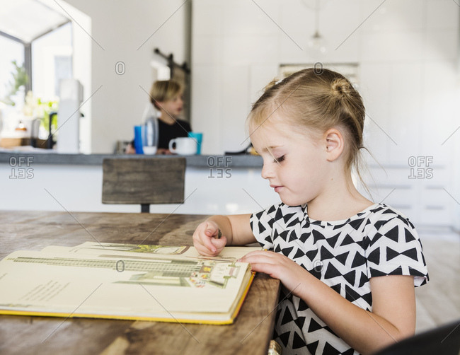 Girl reading picture book at dining table