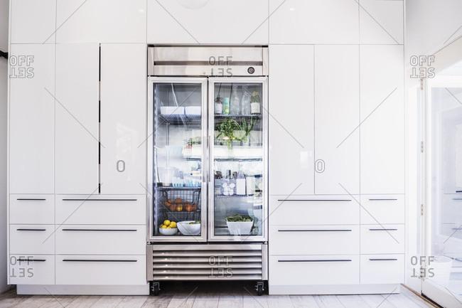 Glass refrigerator in modern kitchen