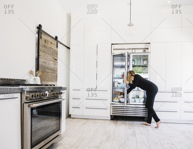 Woman reaching into refrigerator