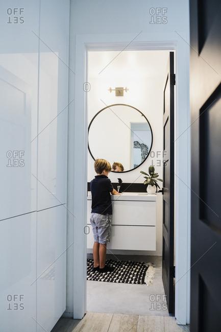 Boy washing his hands in bathroom