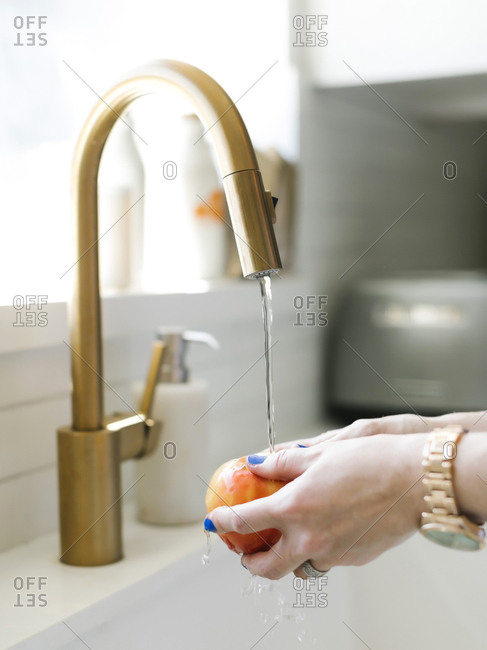 Hands of woman washing apple in kitchen sink