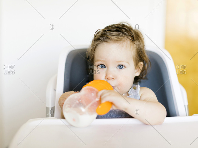 Baby girl drinking in high chair