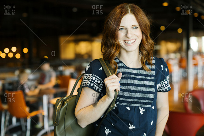 Smiling mid adult woman holding backpack in cafe