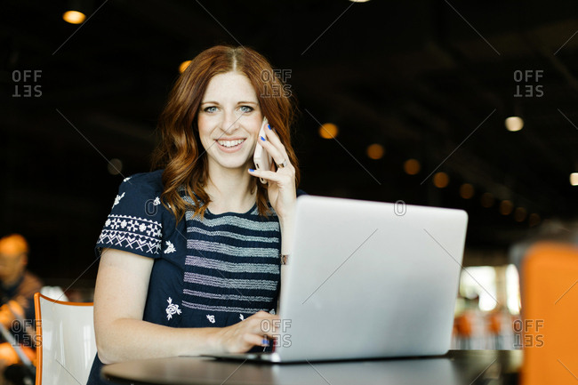 Smiling mid adult woman using smart phone and laptop