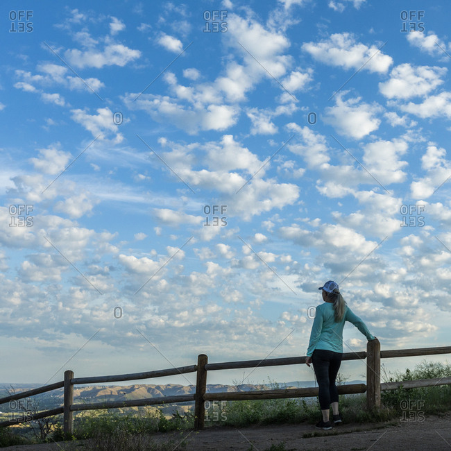 Rear view of mature woman by fence under clouds in Boise, Idaho, USA