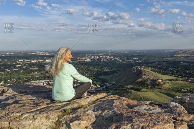 Mature woman sitting on rocks in Boise, Idaho, USA