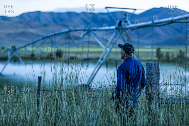 Senior man standing in field by irrigation system