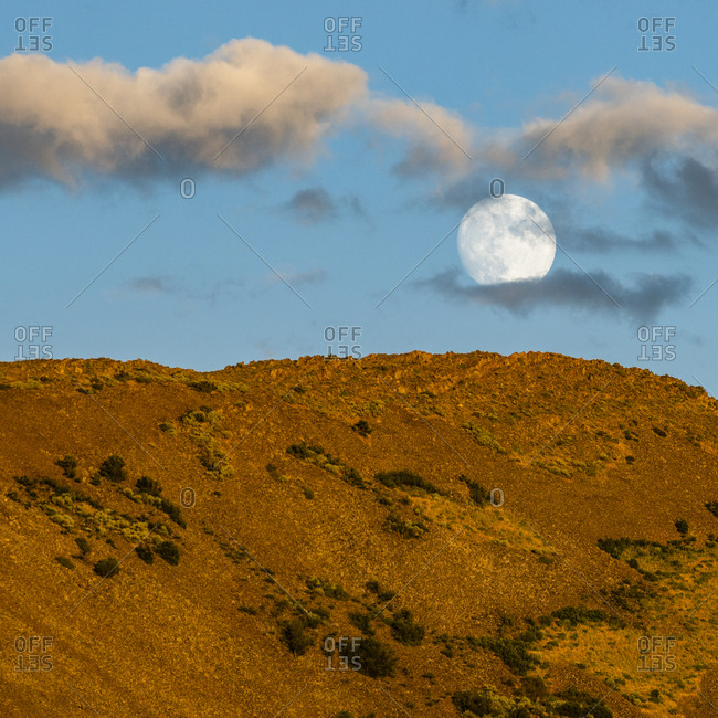 Full moon over brown hill at sunset in Picabo, Idaho, USA