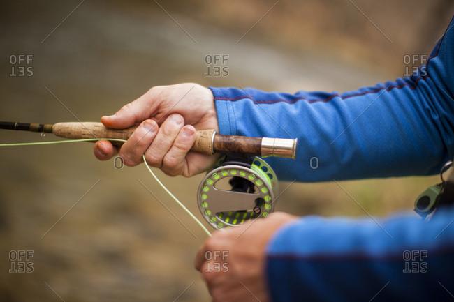 Man's hands holding fishing rod