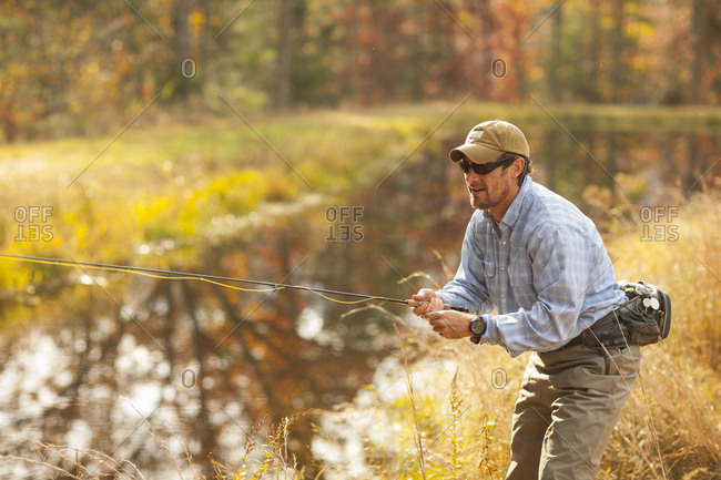Man fly-fishing in river during autumn in Giles County, Virginia, USA