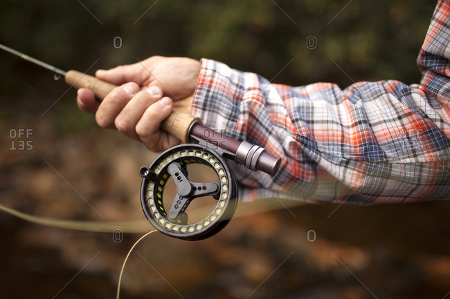Hand of man holding fishing rod
