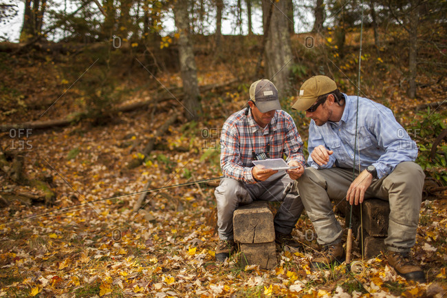 Men with fishing rods and box sitting on logs during autumn